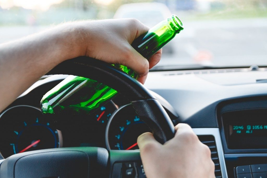 person driving with bottle in hand