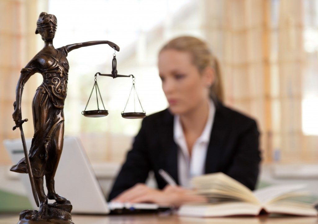 Statue of justice with lawyer typing in the background
