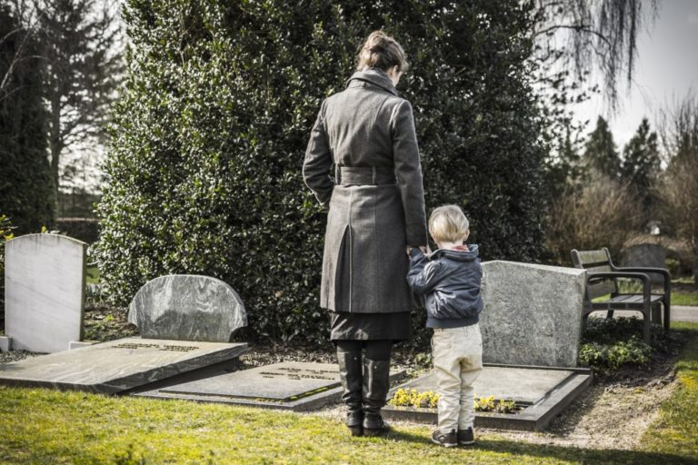 parent and child mourning on grave